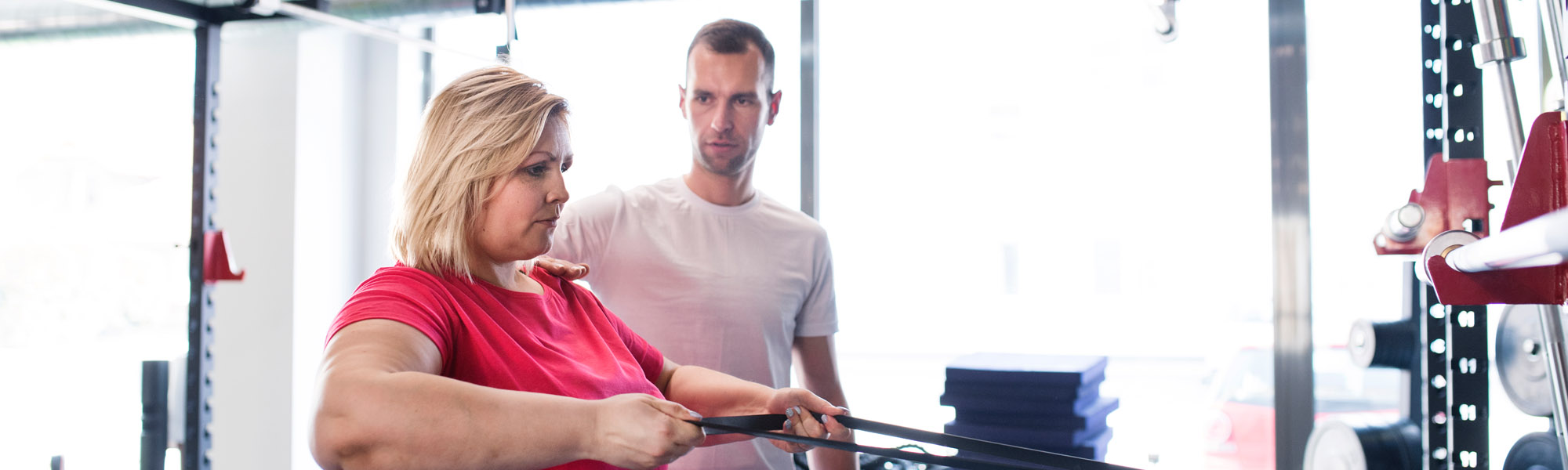male trainer helping woman with workout bands in gym