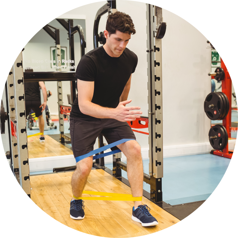 circle image of a young male working out legs with bands