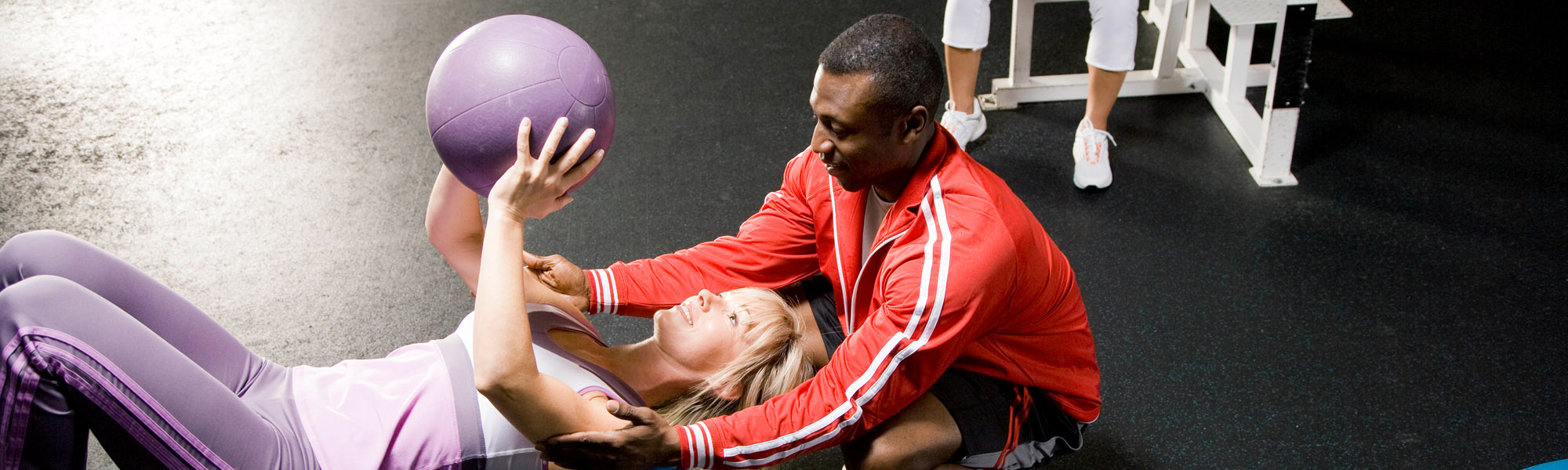 african american trainer helping young white woman workout with medicine ball equipment